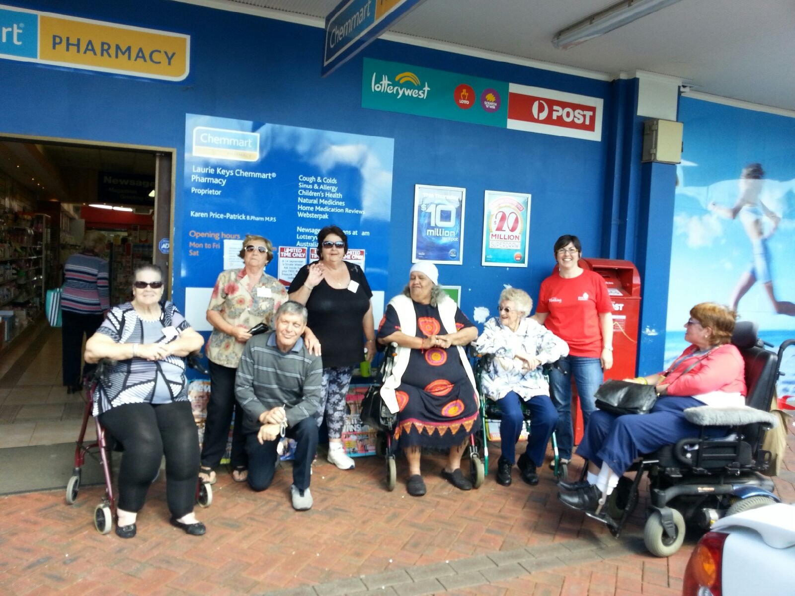 Walking group members posing outside the pharmacy